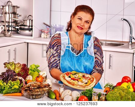Mature woman preparing pizza at kitchen. Near a lot of vegetable. She is happy.