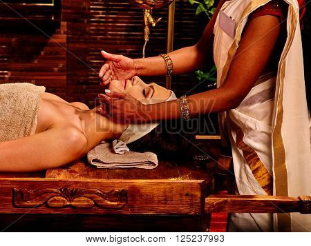 Woman doing facial massage in tropical spa in Indian. SPA salon decorated with bamboo.