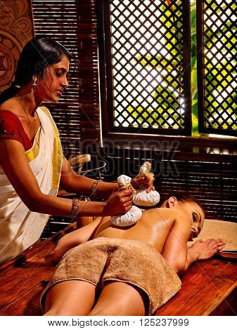 Indian masseur makes Ayurveda massage with herbal bags in front of a wooden window.
