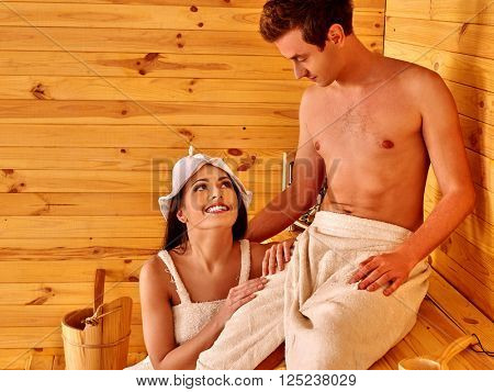 Loving couple relaxing at sauna. Very happy. Wooden bench.