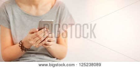 Close-up Of Female Hands Holding Cell Phone. Young Woman Texting On Mobile Telephone On The Gray Wal