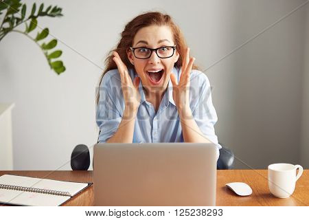 Portrait of a cute redhead girl wearing glasses and blue shirt screaming with excitement and joy while working on her laptop. Headshot of an excited female student with winning expression on her face