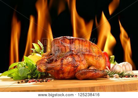 Roasted chicken and various vegetables on a chopping wood
