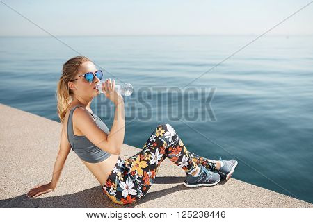 Portrait Of A Fit Young Woman Resting After Successful Jogging Workout Outdoors. Pretty Athlete Blon