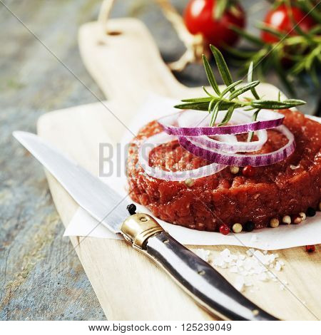 Raw Ground beef meat Burger steak cutlet with seasoning on vintage wooden boards