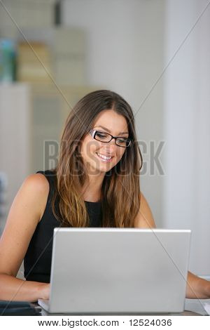 Active woman in office with laptop