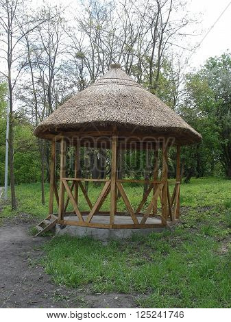 Thatched wooden gazebo,  roofed structure in a park