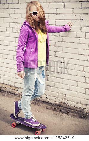 Blond Teenage Girl On A Skateboard