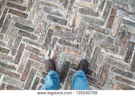 Male Feet  In Jeans On Old Cobblestone Pavement