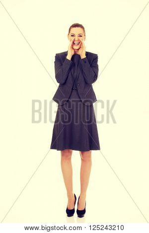 Young smiling business woman screaming loud or calling someone