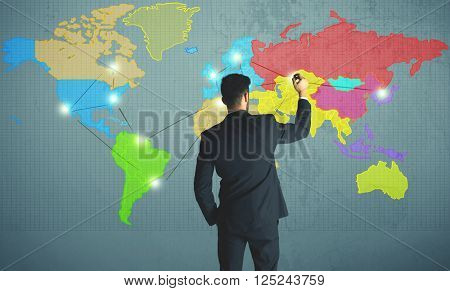 Young businessman drawing map on wall, social network concept