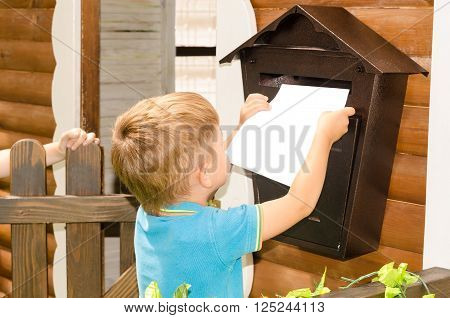 Boy throws a letter in a mailbox