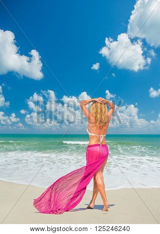 woman with beautiful pink sarong on tropical beach resort