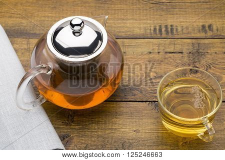 Glass cup of green tea and teapot on wooden background