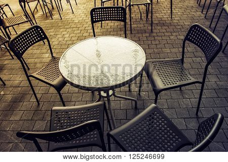 Set of metal chairs and tables on stone pavement in garden restaurant. It is closed.