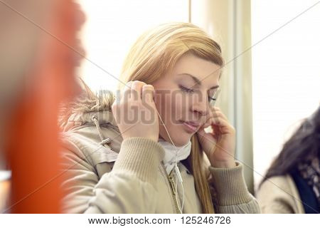 Single beautiful young woman in coat and scarf using earphones while sitting on buss or train