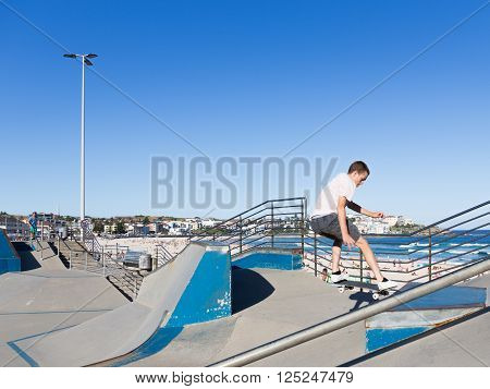 Sydney - March 1 2016: skate boarder performs tricks in Sate Park with interesting slides at the beach and people sunbathing by the sea March 1 2016 Sydney Australia