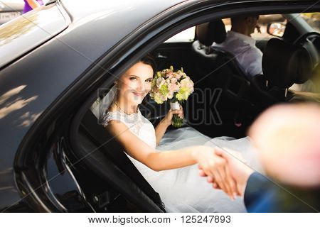 Happy groom helping his beautiful bride out of the wedding car.