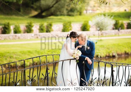 The newly married couple is kissing on the bridge. Sensual photo. Lovely hugging.