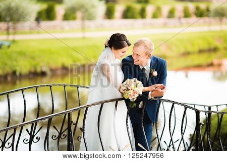 The newly married couple lovely cuddling on the bridge. Sensual photo