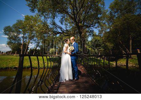 The newly married couple cute cuddling on the bridge. Sensual photo
