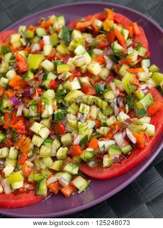 Tomatoes with salsa salad made of cucumbers peppers and onions.