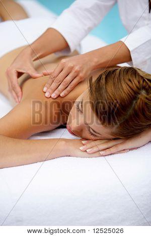 Hermosa mujer con los ojos cerrados con un masaje corporal