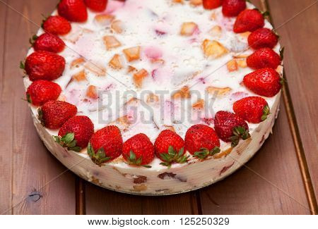 Cake with strawberries gelly yogurt and cherries shot from above over wooden table