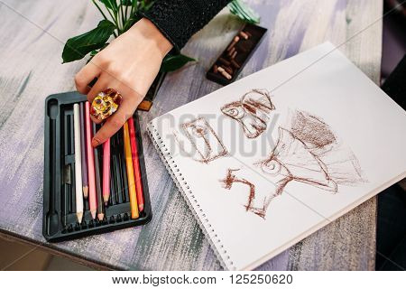 Clothes designer draws a sketch with color pencils. Closeup of drawing process in art workplace. Clothes designer preparing to drawing sketch.