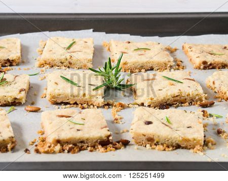Butter cookies with rosemary pignoli and pistachio nuts on baking parchment decorated with rosemary sprigs