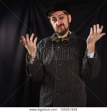 dissatisfied welder in black boilersuit in studio