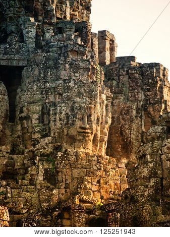 Dramatic view at sunset of one of the many large stone carved faces of Bayon Temple in Angkor Thom Angkor district Siem Reap Cambodia. Vertical shot