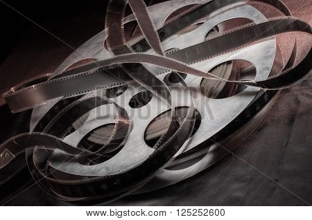 reel of film standing on a black table with black background