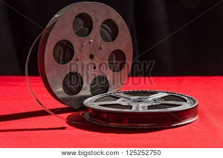 reel of film  on a red table with black background ** Note: Visible grain at 100%, best at smaller sizes