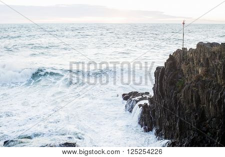 Waves breaking over cliff in Ligurian sea during a stormy winter day