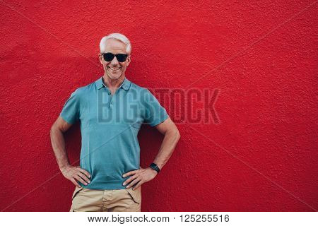 Portrait of confident mature man standing his hands on hips against red background.