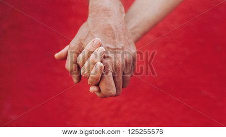 Close up of man and woman holding hands against red background. Affectionate couple holding hands.