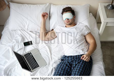 Young man sleeping with blindfold in bed at home