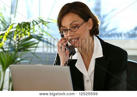 Business woman talking on the phone in the office