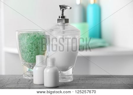 Liquid soap and green salt on shelf in bathroom