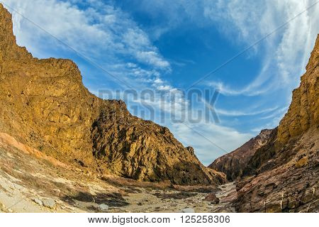 Picturesque and multi-color Black canyon in ancient Eilat mountains. Israeli warm winter. Photo taken fisheye lens