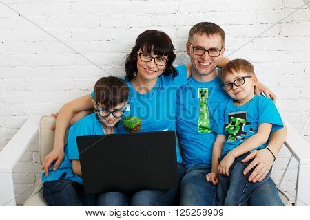 Happy family of four wearing eyeglasses. Parents and children, boys siblings in glasses with laptop computer. In white interior indoors.
