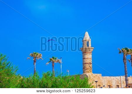 Minaret, walls and palm Arab period Caesarea. In the blue sky flying controllable parachute.  National park Caesarea