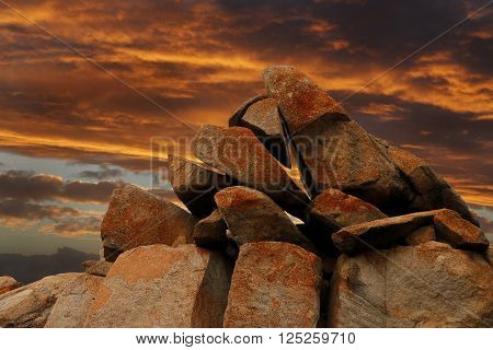 The sun sets spectacularly in golden hues on the rocky outcrop