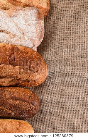 Five different loaves of bread on a wood table with copy space. Vertical format.