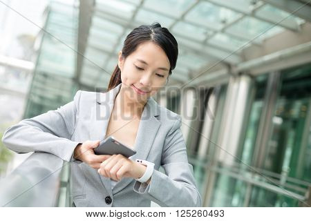 Business woman using smart watch and cellphone