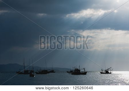 Scenery of fishing boats and yachts with sunlight shining through cloudy sky and reflections of golden clouds on smooth water in Thailand