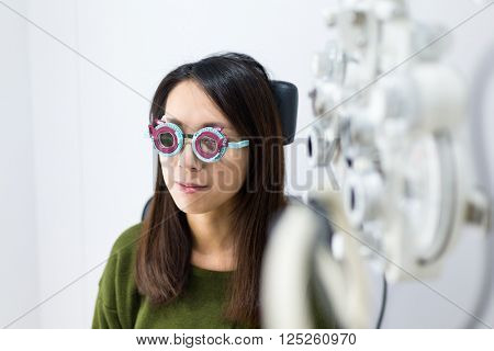 Woman doing the eye sight test in optical clinic