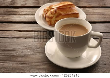 Milk tea with eclairs on wooden background.