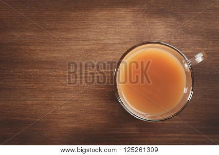 Tea with milk on wooden background.